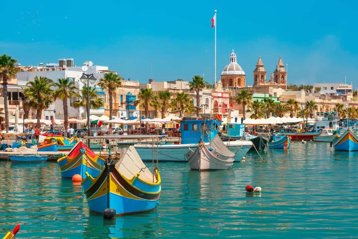 Backpacking destinations in Europe for College Students: Traditional eyed colorful boats Luzzu in the Harbor of Mediterranean fishing village Marsaxlok Malta